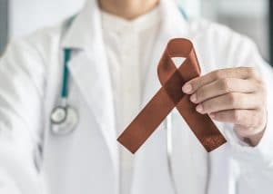 Copper Brown Awareness Ribbon on doctor's hand, symbolic color for Anti-Tobacco, Colon Colorectal Cancers, Herpes Simplex Virus (HSV 1 and HSV 2)