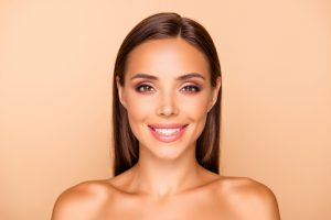 Close up picture photo of lovely charming pretty brown-haired lady with her naked shoulders she isolated on pastel beige background make white beaming big smile
