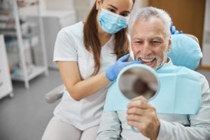 Elderly man and his young female dentist smiling while looking in the mirror in dental clinic
