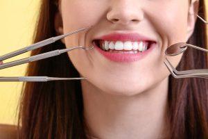 Beautiful smiling young woman with dental tools, closeup