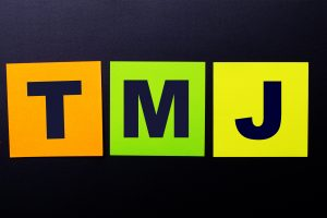 Bright multi-colored paper stickers on a black background with the text TMJ