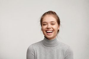 Headshot of good-looking lucky woman with tied hair pure skin and broad smile being happy to watch at camera. Sincere female with beautiful appearance wearing casual clothes isolated over white wall