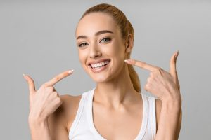 Orthodontic concept. Happy girl showing her beaming white teeth with two forefingers, grey background