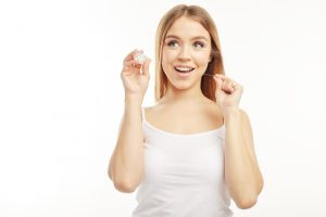 Smiling blonde on the white background showing how to use dental floss which she holds in her hands.