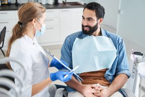 Young female dentist showing the paper to a satisfied smiling bearded man client of the dental office. People talking and looking at each other. People, medicine, stomatology and health care concept