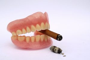 Cigar with dental prosthetic as anti smoking concept
