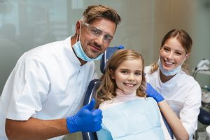 Image of a cute happy beautiful child girl sitting in medical dentist center with two doctors.