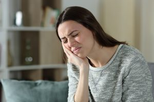 Stressed woman complaining suffering toothache sitting on a couch at home
