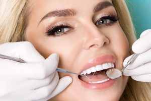Young beautiful woman with beautiful white teeth sitting on a dental chair. The dentist cures her teeth.