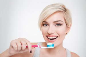 Happy beautiful woman brushing teeth isolated on a white background