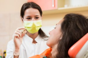 Dentist woman holding patient's tooth in hand
