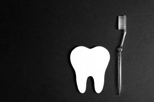 White paper tooth with toothbrush on black background. Dental health concept. Dentist day concept. Flat lay, top view, copy space. Black and white image.