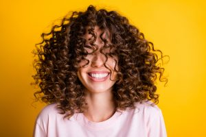 Headshot of laughing cheerful girl with curly hairstyle wearing t-shirt white toothy smile isolated on bright yellow color background.
