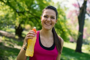 Smiling young woman holding energy drink outdoors in a park.