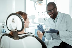 Concentrated dark-skinned doctor. Openly-smiling dentist carrying plastic model of the jaw and showing right way of brushing