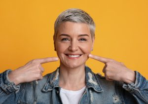 Perfect Smile. Mature woman pointing on her strong healthy teeth and looking at camera while posing over yellow studio background, closeup portrait