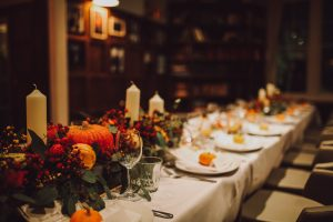 Thanksgiving table setting with automnal decorations, pumpkins, glasses and plates. Holidays, catering and hospitality concept.