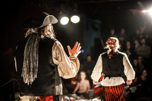 A creative shot with shallow depth of field from behind two performing arts entertainers dressed as pirates on a theater stage during comedy act.