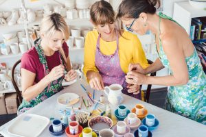 Teacher showing two women in workshop how to paint self-made dishes