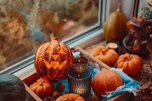 Halloween cozy mood composition on the windowsill. Lighting jack-o-lantern, decorative pumpkins, cones, candles on wooden tray and straw napkin, warm plaid. Hygge halloween home decor. Selective focus.