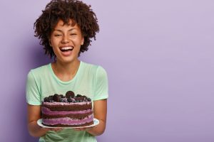 Happy birthday girl laughs joyfully, holds big tasty fruit cake, likes eating sweet food, improves mood with raising sugar in blood, has positive face look, stands over purple background, blank space